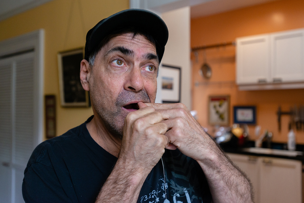 David Tuller flosses his teeth as he walks around his San Francisco home. After he was diagnosed with periodontal disease, Tuller underwent several extractions, titanium implants in his jaw, multiple bone grafts and a series of gum surgeries. (Heidi de Marco/KHN)