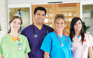 four nurses in bright colored scrubs
